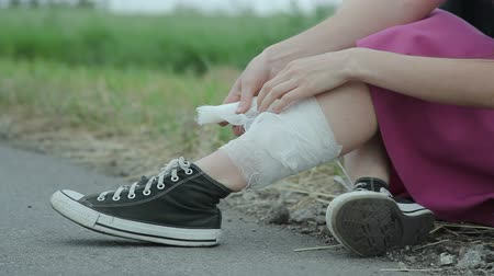 ferimento : Young girl wrapping her leg with bandage Stock Footage