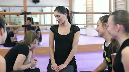 fegyelem : Melitopol, Ukraine. Classes at a private dance school. December 26, 2017. Attrative female teacher talking and smiling in the ballet studio. Dance school trainer explaining something to her students
