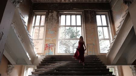 abandonar : A woman in a long dress is walking up the stairs in an abandoned house