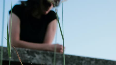 A view of a green stems, behind which is a sorrowful girl, leaning against the bridge