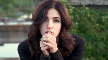 A sad young woman with beautiful green eyes looks straight and touch her hair, leaning her face against crossed fingers