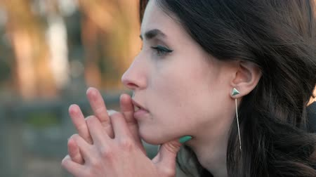 A view of sad young womans beautiful face, with eyes red from tears, leaning against crossed fingers