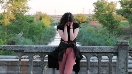 A view from right to left of a sad woman, standing on a bridge, who sadly covers her face with hands and starts Stock mozgókép