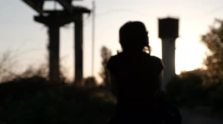 An unfocused silhouette of a young woman, walking away into the sunset
