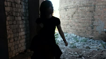 A young woman lookes around and rushes while going through the ruined building