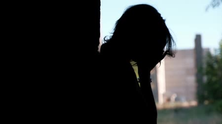 brick factory : A silhouette of a sad young woman is leaning against the wall and covering her face with hands, feeling despair Stock Footage