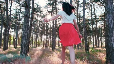 A young beautiful woman is happily running among numerous pine trees in the woods. View from the back. Slow motion