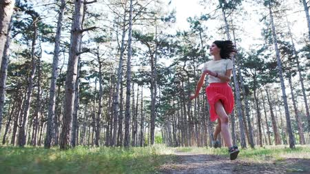A young beautiful woman is happily running along the road among numerous pine trees. Slow motion