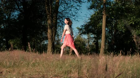 A young beautiful woman walks happily in the woods, touching her dress, hopping and raising her hands to touch the branches of the trees Stock mozgókép