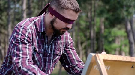 A blindfolded man is passionately working on his picture , being in the woods