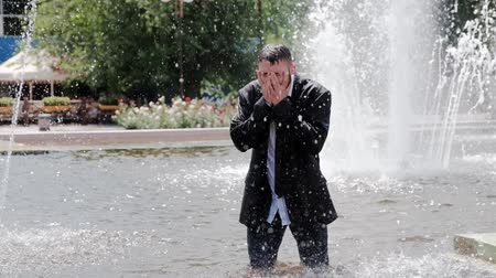 A man is walking in a fountain, covering his face with hands and feeling all the sadness in the world