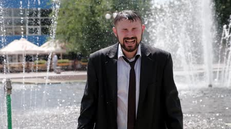 A man, who stands in a fountain, cries bitterly