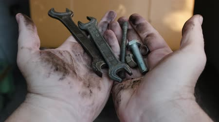 Mans dirty hands hold various tools and then drop them