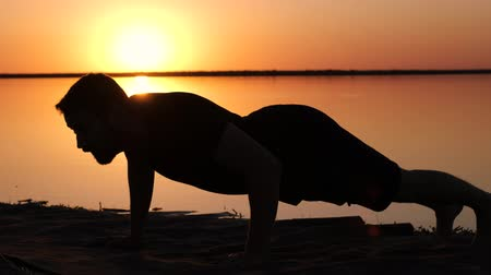 A silhouette of a man doing push ups on a seacoast against the sunset