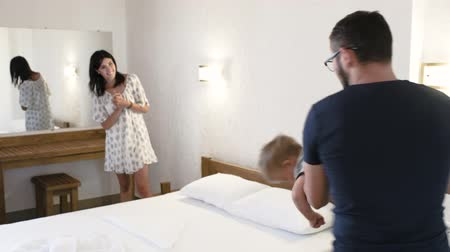 Parents play with their child in a hotel room. Father spins, holding his son in his hands and then puts him cautiously onto the bed. Meanwhile mother claps hands excitingly