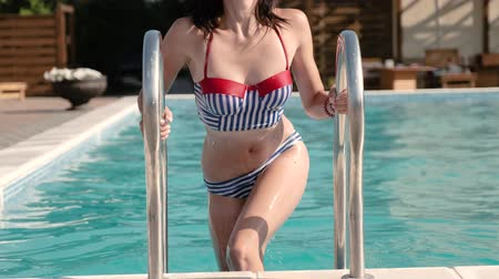 A young beautiful woman in a swimsuit gracefully comes up from the swimming pool