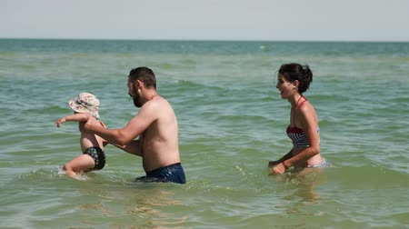 Happy parents play with their child in the sea. Father is spinning, holding his son in his hands and mother is trying to catch him