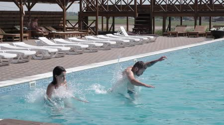 A cheerful couple runs and jumps into the swimming pool Stock mozgókép