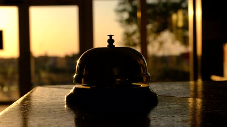 sinos : Somebody rings the bell, lying against windows, through which still come lights of the setting sun