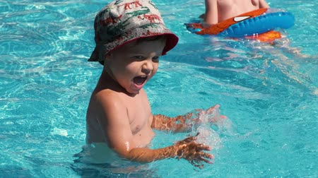 A happy child marrily claps his hands while walking in a swimming pool