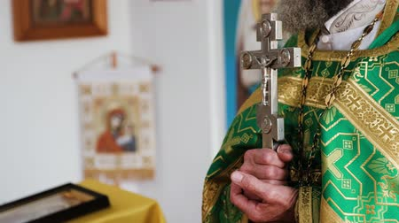 believer : A view of a cross in hands of a priest, saying the prayer