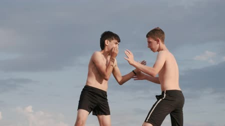 A view of two boys fighting on a training far away from the city