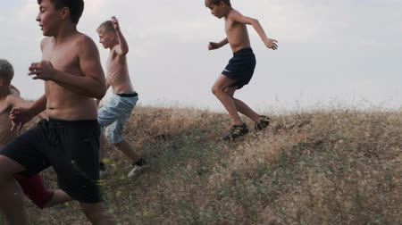 A view of running children, competing on a training in a field Stock mozgókép