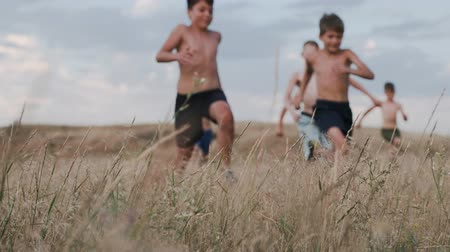 A view of children, competing in running in a field with yellow grass