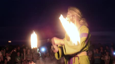 зажигание : A man in ethnic costume juggling with the fire against the night. Slow motion