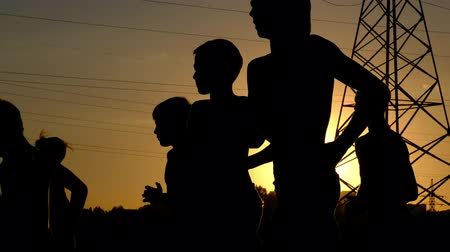 competitivo : Silhouettes of young boys, jogging on a training against the sunset
