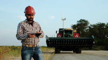 hardhat : The engineer of wind power plants stands next to agricultural machinery against the background of wind power plants. Stock Footage