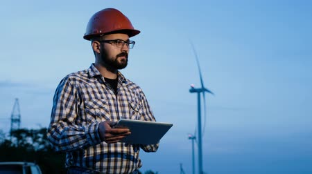 hatékonyság : Engineer-builder against the background of wind power plants in the evening.