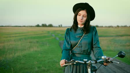 nevinný : Portrait of a brunette in a hat in a vintage dress and with a bicycle in the steppe.