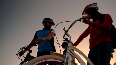 estepe : A married couple on bicycles in the background of the rising sun go on a bike ride. Stock Footage