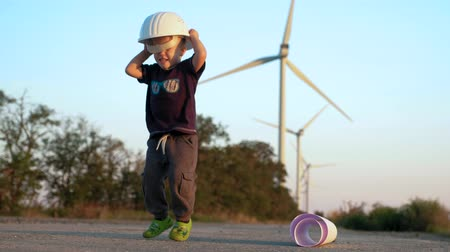 grass flowers : A little boy plays with constructor helmet. He puts it on and jumps until it falls down