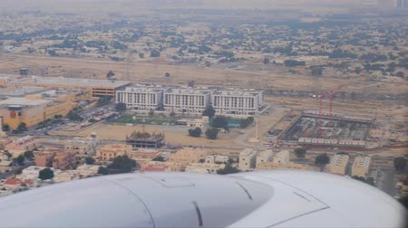 flap : view out off landing aircraft window across engine nacelle on landscape with Arab city and highway downwards