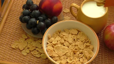 yelow : Cornflakes in a bowl with milk and fruits
