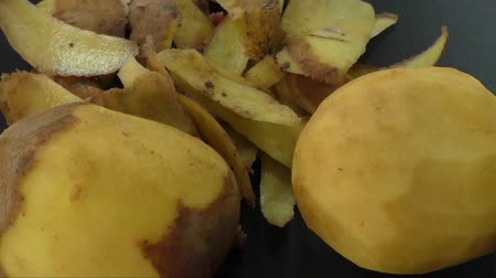 brambory : Peeled potatoes and potato peel on the black background Dostupné videozáznamy