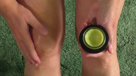 конопля : Woman putting ointment cream on bad injured knee. Sport training gym and health care