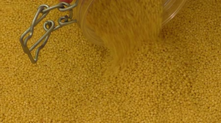 peeled grains : Millet grains falling on a pile of millet