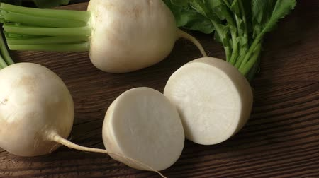 daikon radish : Tasty fresh red round white japanese radish with green stems and leaves Stock Footage