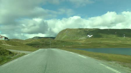 previously : Driving a car on a road in Norway. Beautiful landscape in Norway with lake and road. Road in the mountains of Norway.