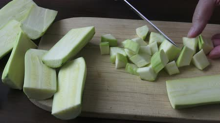 крупные планы : Woman holding kitchen knife, chopping peeled zucchini. Healthy eating concept.