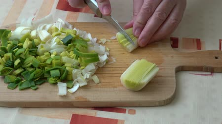 pırasa : Natural fresh cut cut leeks on the wooden cutting board. Closeup of sliced leek. Slices of the fresh green leek. Chopped Leek. Fresh vegetables. Stok Video