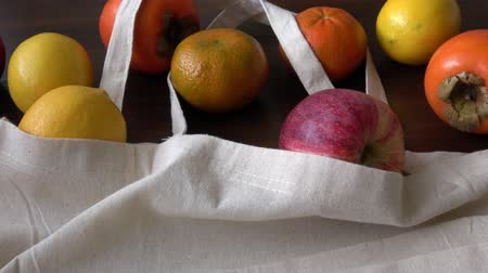 Eco bag with fruits. Zero Waste Use Less Plastic Concept. Fresh organic fruits in cotton fabric on wooden table