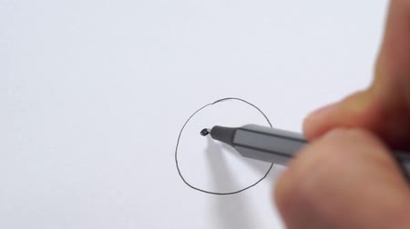 Drawing an emoji on a piece of paper.