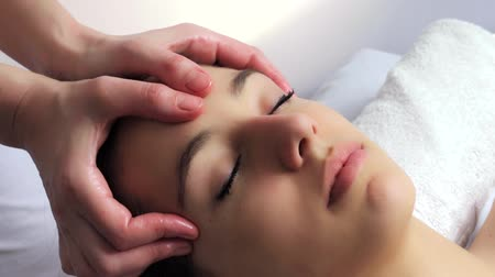 Close up locked down head shot of young woman having curative facial massage. Therapist applying pressure with thumbs on forehead Dostupné videozáznamy