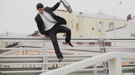 связать : The guy is an office worker in a hurry, jumping over obstacles. Parkour in a business suit. The theme of business and Finance. Slow motion.