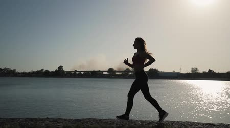 sztafeta : Young athletic caucasian girl runs along the lake on a sunset background. Far away smoke from the fire. Slow motion. Overall plan. Wideo