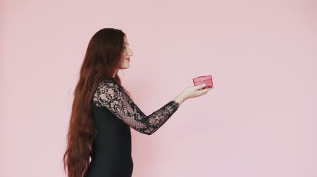 demonstrar : Young Caucasian red-haired girl holds out a gift in the palm of your hand on pink background. Slow motion. theme of 8th of March. Vídeos